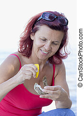 Woman eating fresh oyster - Cute smiling woman eating fresh...