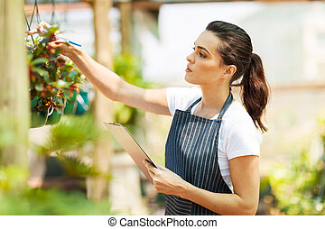 florist checking flowers condition in greenhouse