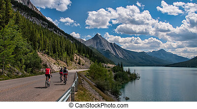Three Cyclists On Road With Mountains - Three cyclists on a...