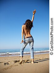 dancing jeans woman at beach - woman back at Arenal Moris...