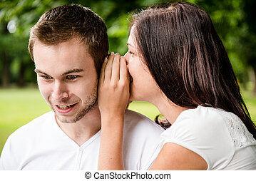 Tell me secret - whisper - Young woman whispering to man...