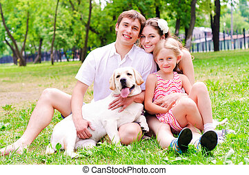 Happy young family with Labrador is resting in the park