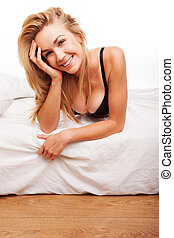 Sexy smiling blonde on her bed - Sexy smiling blonde woman...