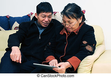 Asian elder couple playing with touchscreen tablet - Asian...