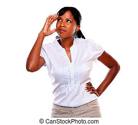 Stressed young woman with headache looking up against white...