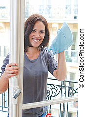 Young woman cleaning windowpane - Smiling woman cleaning the...