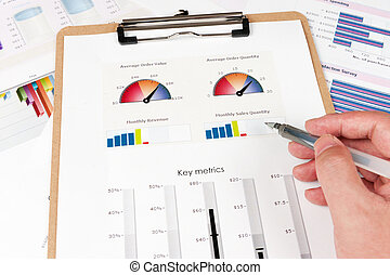 Business graph printed on the white paper with a hand...