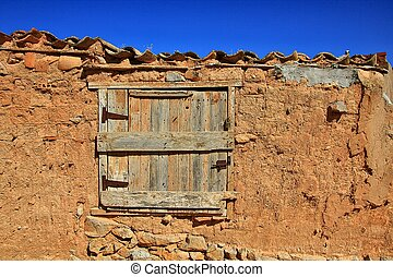old wooden window in the house of adobe and mud