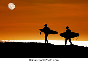 Surfers walking to the ocean for a sunset ride - Surfers...