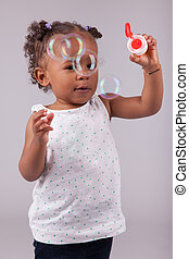 Little African American girl playing with soap bubbles -...