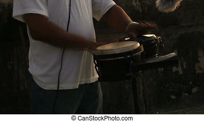 Bongo largo - Two hands playing son music with a bongo drum,...