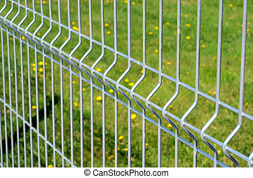 Metal fence - Chromium metal fence with green grass in...