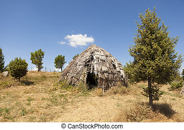 Traditional straw hut in greek country, on a sunny day