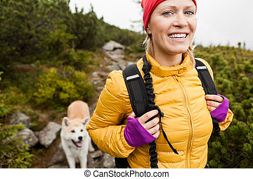 Woman hiking in mountains with akita dog, Karkonosze...