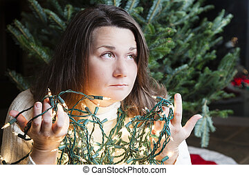 Holiday woes - Young woman sitting next to Christmas tree...