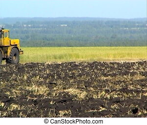 Agriculture - The Tractor plows the land.