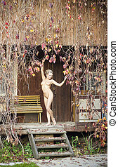 Nude girl is standing on the porch.
