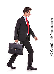 serious business man holding a briefcase and walking - side...