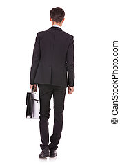 back view of a business man standing and holding a briefcase...