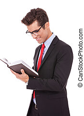 business man wearing glasses and reading a book