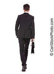 back view of a business man holding a briefcase and walking...