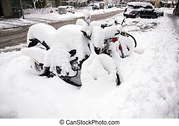 Snowed under - Motor bikes parked on the street are covered...