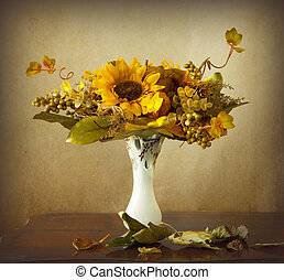 Autumn leaves and dried sunflowers - An autumnal bouquet,...