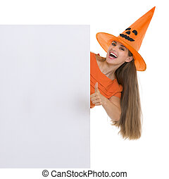 Happy woman in Halloween hat showing blank billboard and thumbs up