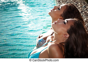 relax by the pool - two young women relax and take sunbath...
