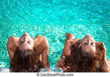 sunbathing in the swimmingpool - two young women relax and...