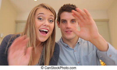 Couple waving and talking at video