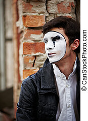 Guy mime against an old brick wall.