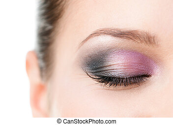 Close up of woman's closed eye with makeup of pink and grey...