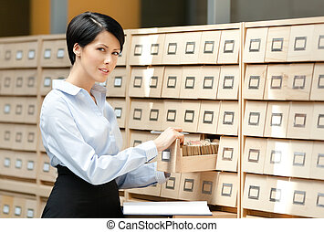 Young woman looks for something in card catalog - Pretty...
