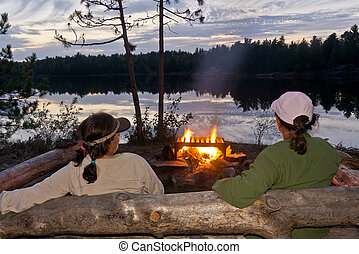 Lakeside Campfire - Two women enjoying a campfire after a...