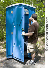 Porta Potty - A young man investigating a blue porta potty...