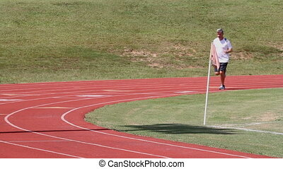 Fitness Running Track - Mature male adult runner turns the...
