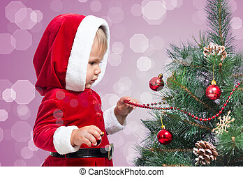 pretty child decorating Christmas tree on bright background