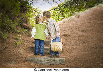 Two Children with Basket Kissing Outside on Steps