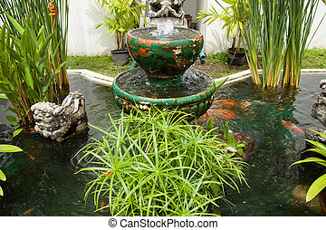 Pond in the garden. - Garden pond with a fountain and a tree...