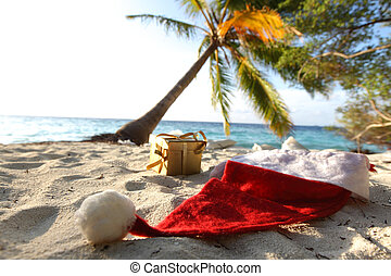 santa vacation - santa hat on sand under palm