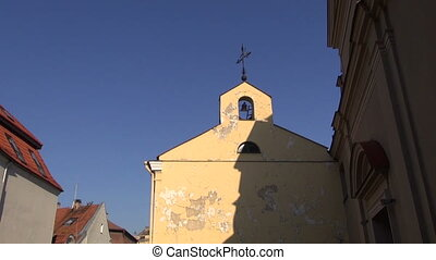 old bell tower with black bell and cross