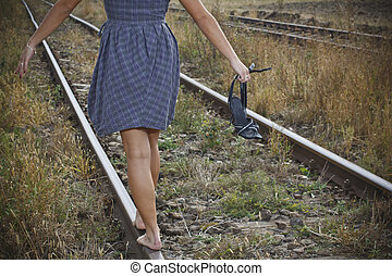 Young woman with shoes in her hand on the railway