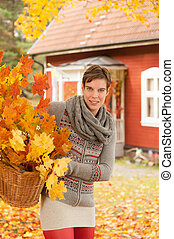 Attractive woman collecting autumn leaves for use in...