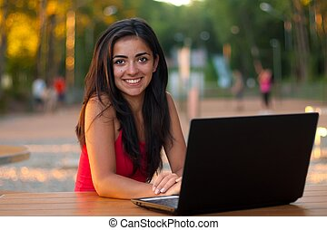 Happy attractive girl with her laptop outdoors - Attractive...