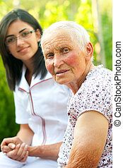 Helping sick elderly woman - A young doctor / nurse visiting...