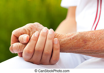 Holding hands - Doctor holding hand of an elderly woman