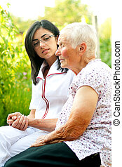 Caring - A young doctor / nurse visiting an elderly sick...