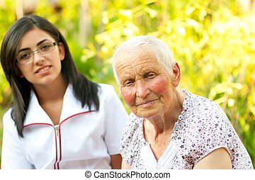 Eldelry woman outdoors with doctor - Young doctor/ nurse...