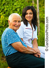 Elderly woman outdoors with doctor / nurse - A young doctor...